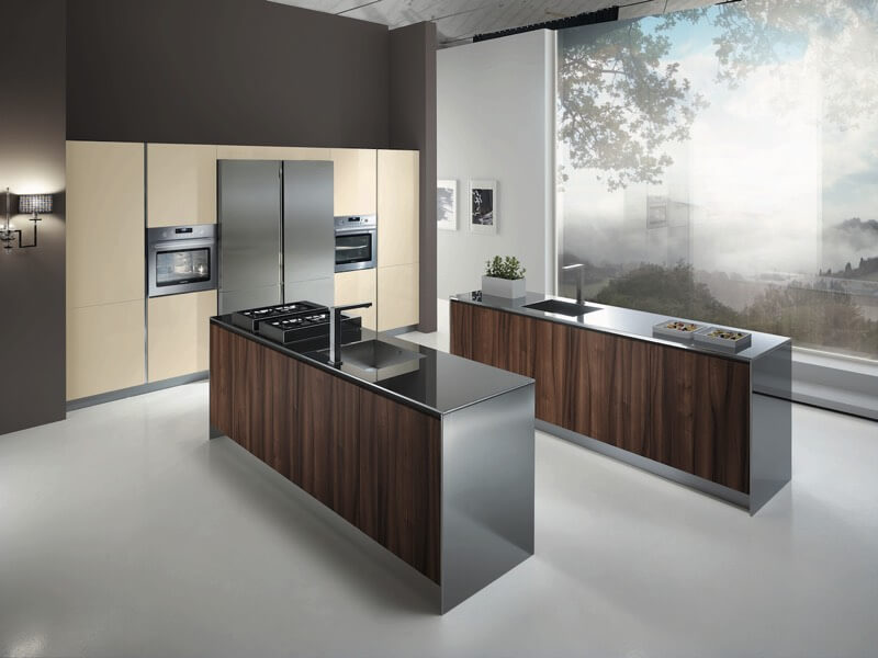 Kitchen features neatly symmetrical look with twin metal and wood islands facing each other next to a beige panel holding twin ovens and the refrigerator. Giant, full height window leaves the space open to the outdoors.