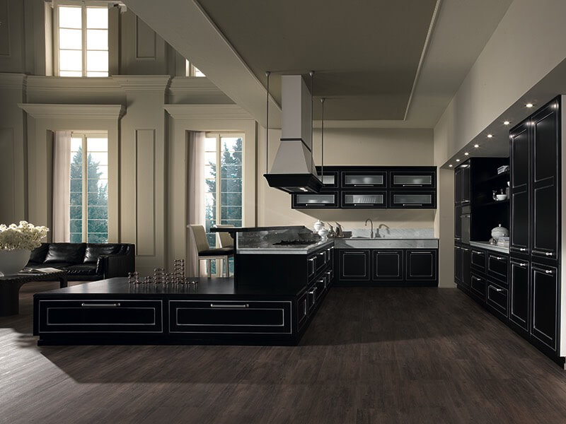 A stunning exercise in contrast, this room features jet black cabinetry throughout with silver accents, over dark hardwood flooring and light beige walls. Dramatic hood vent hangs toward range, while the space opens into two story living room area.