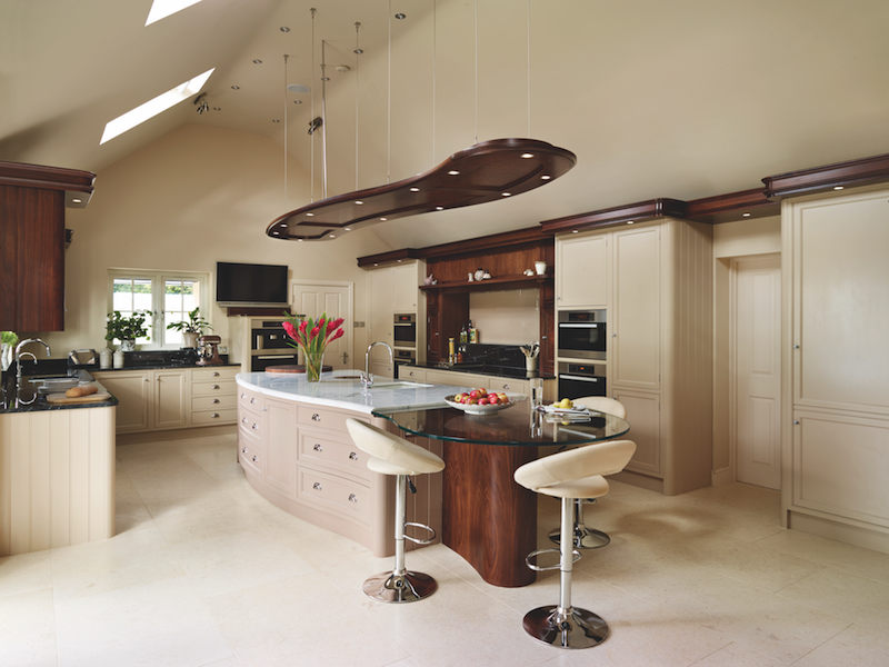An ultra modern design coheres in this kitchen, featuring oblong island shape mirrored in the overhead lighting mount, standing apart in a strictly right-angled kitchen. Cabinetry matches the off-white walls and flooring, with splashes of natural wood, black and white marble, and tempered glass.