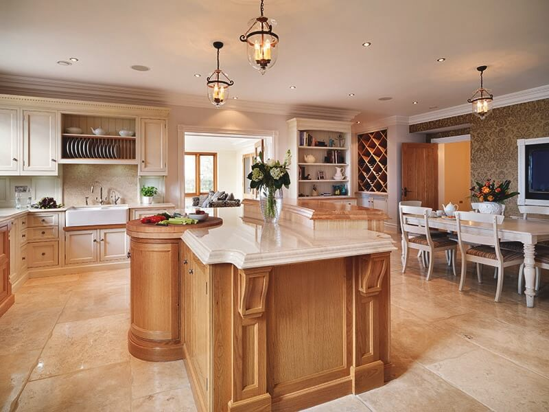 Here we have a kitchen featuring natural wood island with glossy white marble countertop, surrounded by white wood cabinetry over a beige tile floor. Large open space features dining area and large built-in wall wine rack in corner.