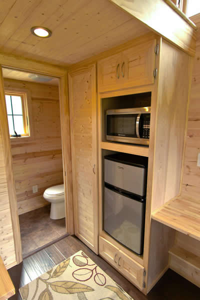 kitchenette features compact refrigerator and microwave in built in shelving with bathroom in background - Compact House Interior
