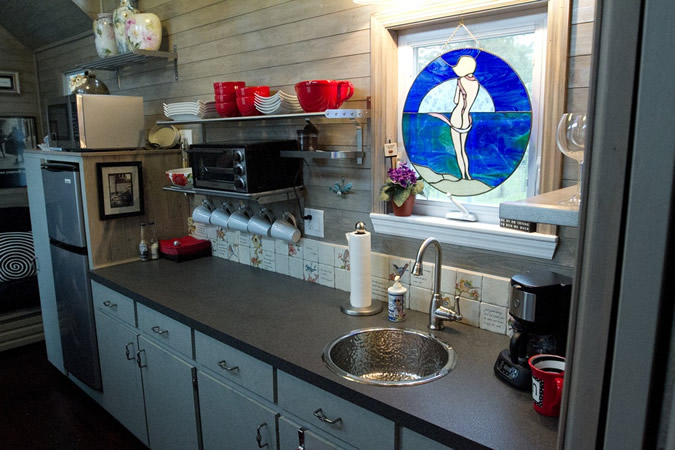 Full Featured Kitchen Holds Lengthy Black Countertop With Sink Under Stained Glass Window Cover