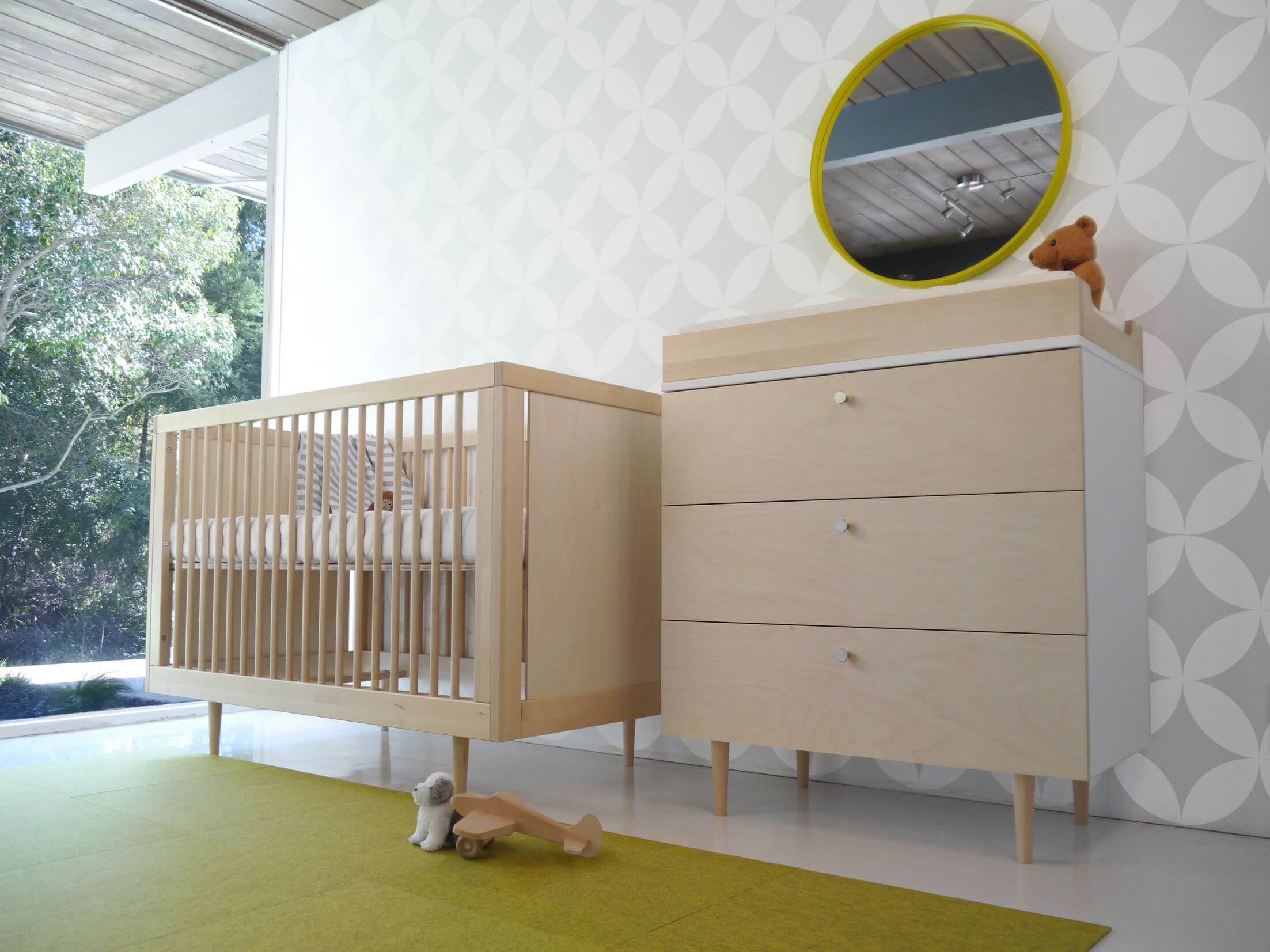 Light yellow and grey bedroom - Light Natural Wood Crib And Matching Changing Table With Dresser Stand Beneath Patterned White And Grey