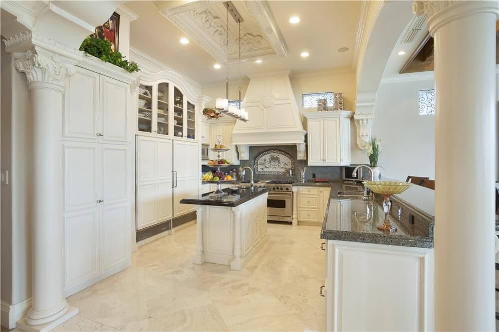 thoroughly white kitchen features marble flooring with ornate cabinetry and island with contrasting black counter top - Marble Kitchen Design