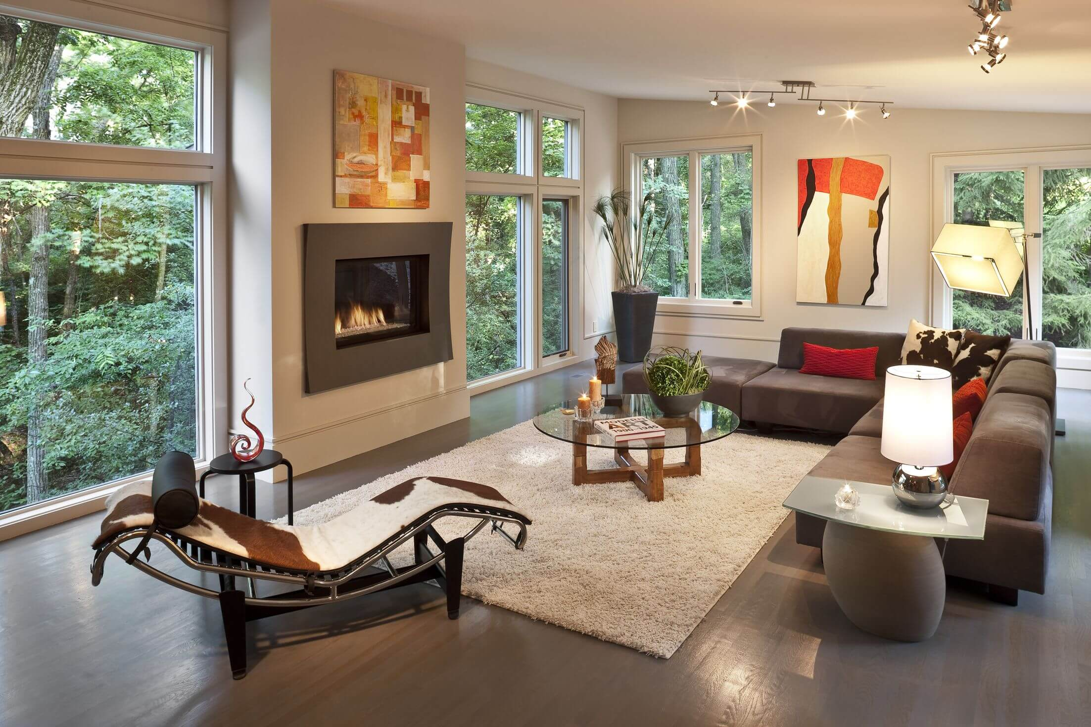 Sloped White Ceiling Over Dark Wood Flooring In This Living Room Holding Modern Armless Brown Sofa