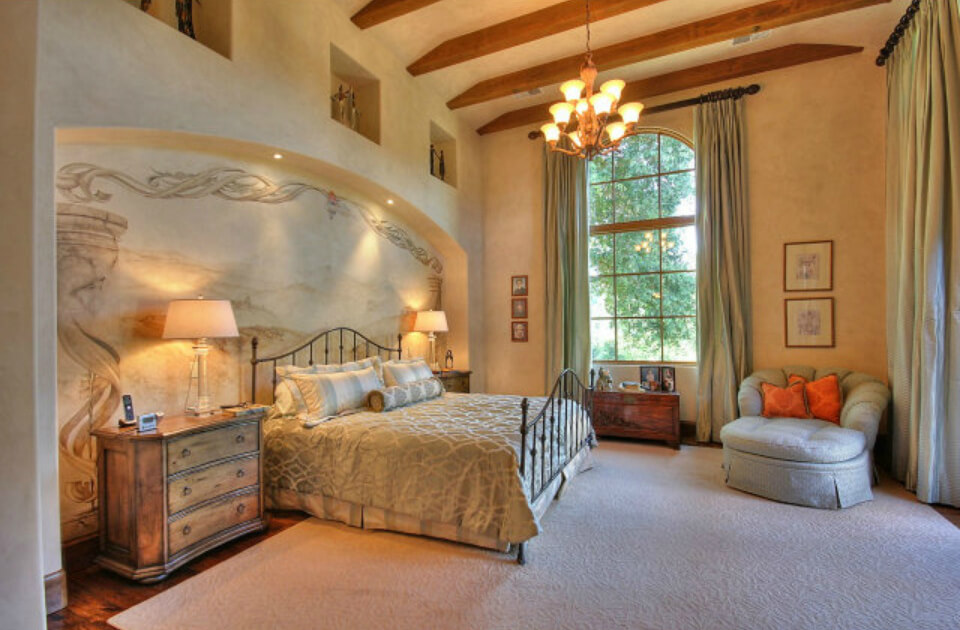 Spacious master bedroom with recessed wall with mural.  Small sitting area and plenty of open space.  Arched windows flood the room with plenty of light.
