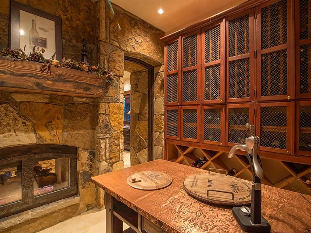 Wine cellar features extensive built-in wood shelving and cabinetry, with second stone pass-through fireplace.
