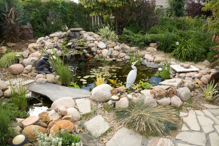 intricate stone waterfall and pond is approached on this broken flagstone walkway