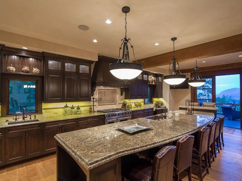Kitchen as seen from opposite angle, highlighting under-cabinet lighting, natural hardwood flooring, and French doors opening to balcony deck.
