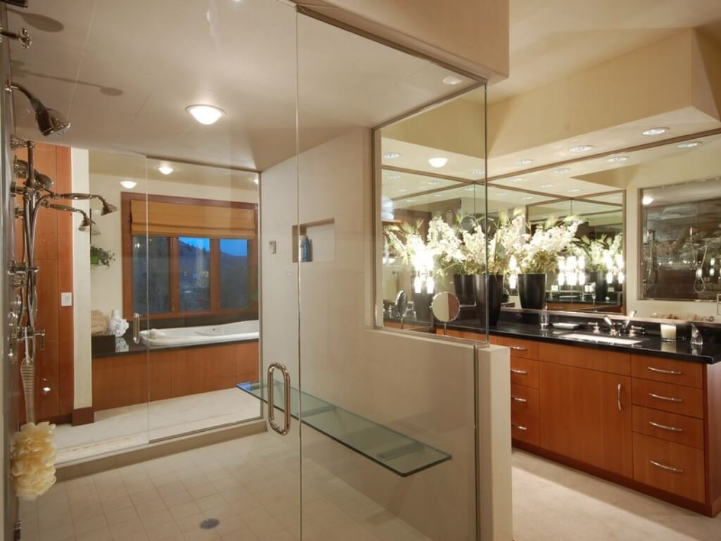 Spacious master bathroom with large glass shower, double vanity and large tub alcove under a window.