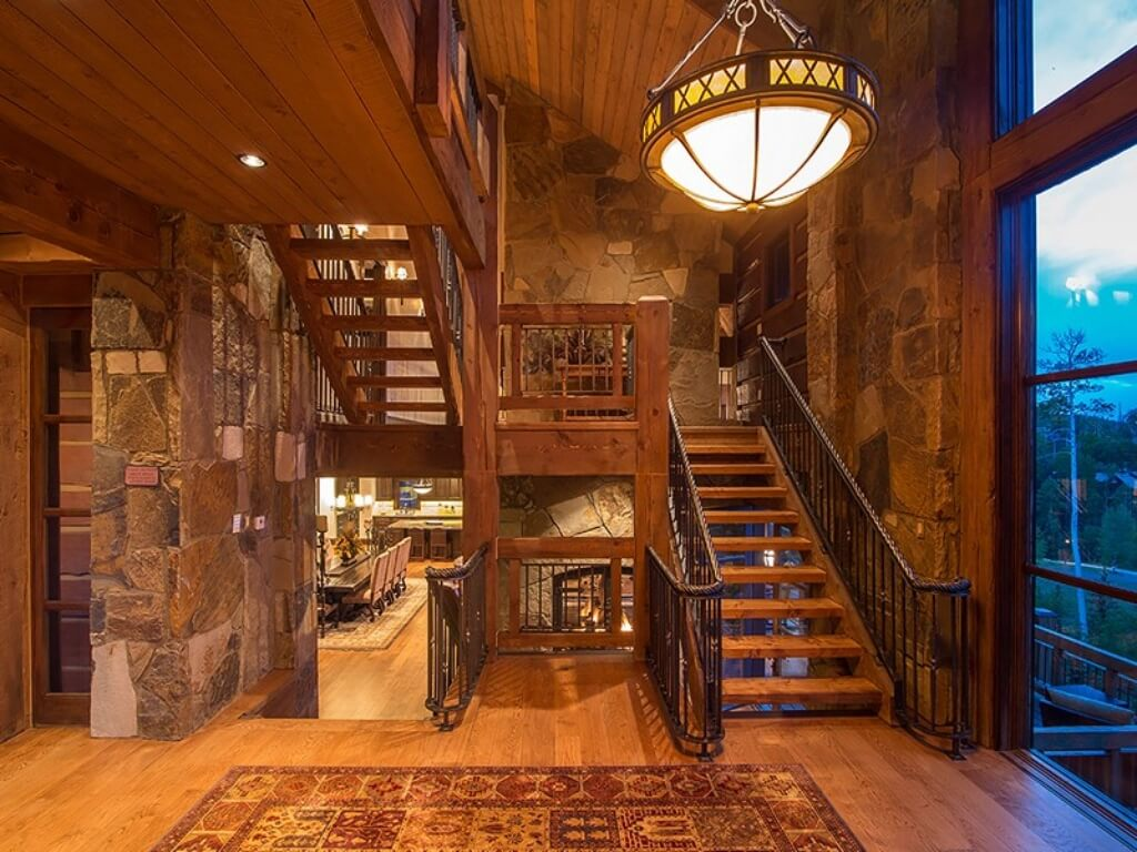 Main staircase in natural wood and wrought iron curves around stone stone walls beneath modern, spherical chandelier.