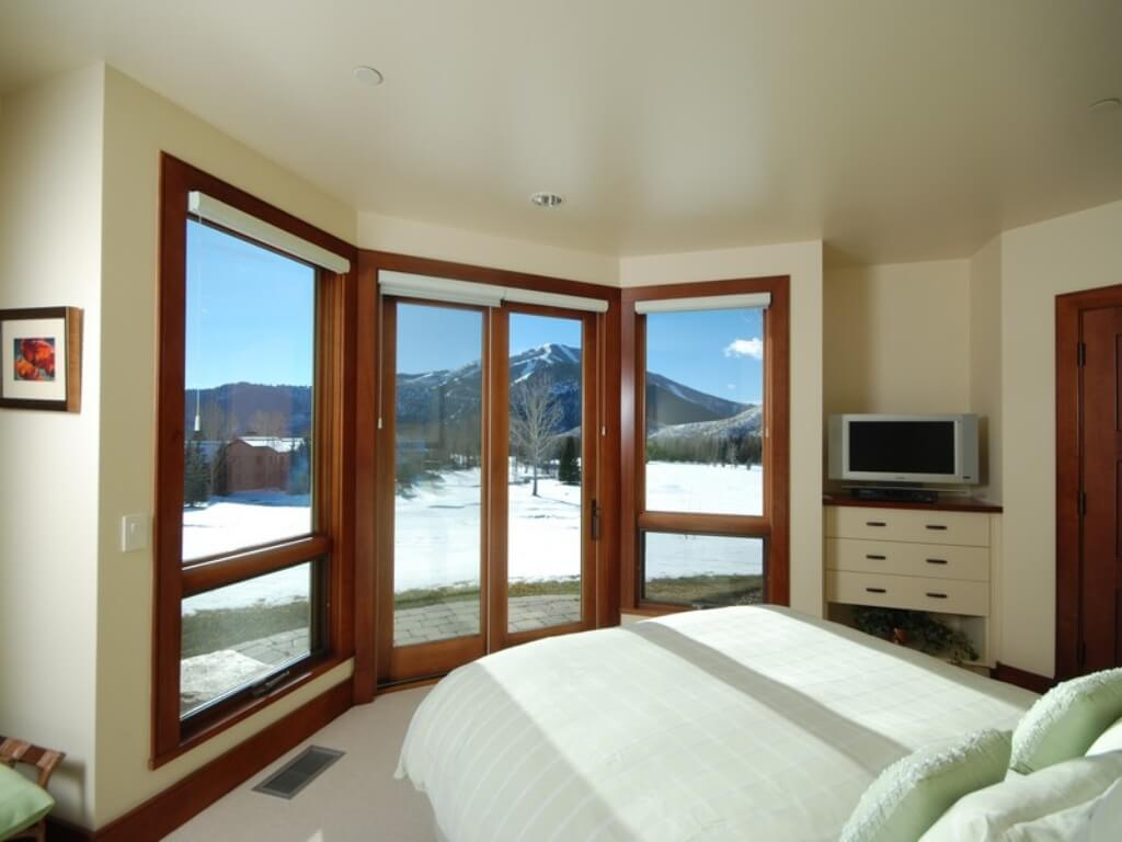 The second bedroom features built-in dresser drawers and bay window with glass doors leading to small patio.