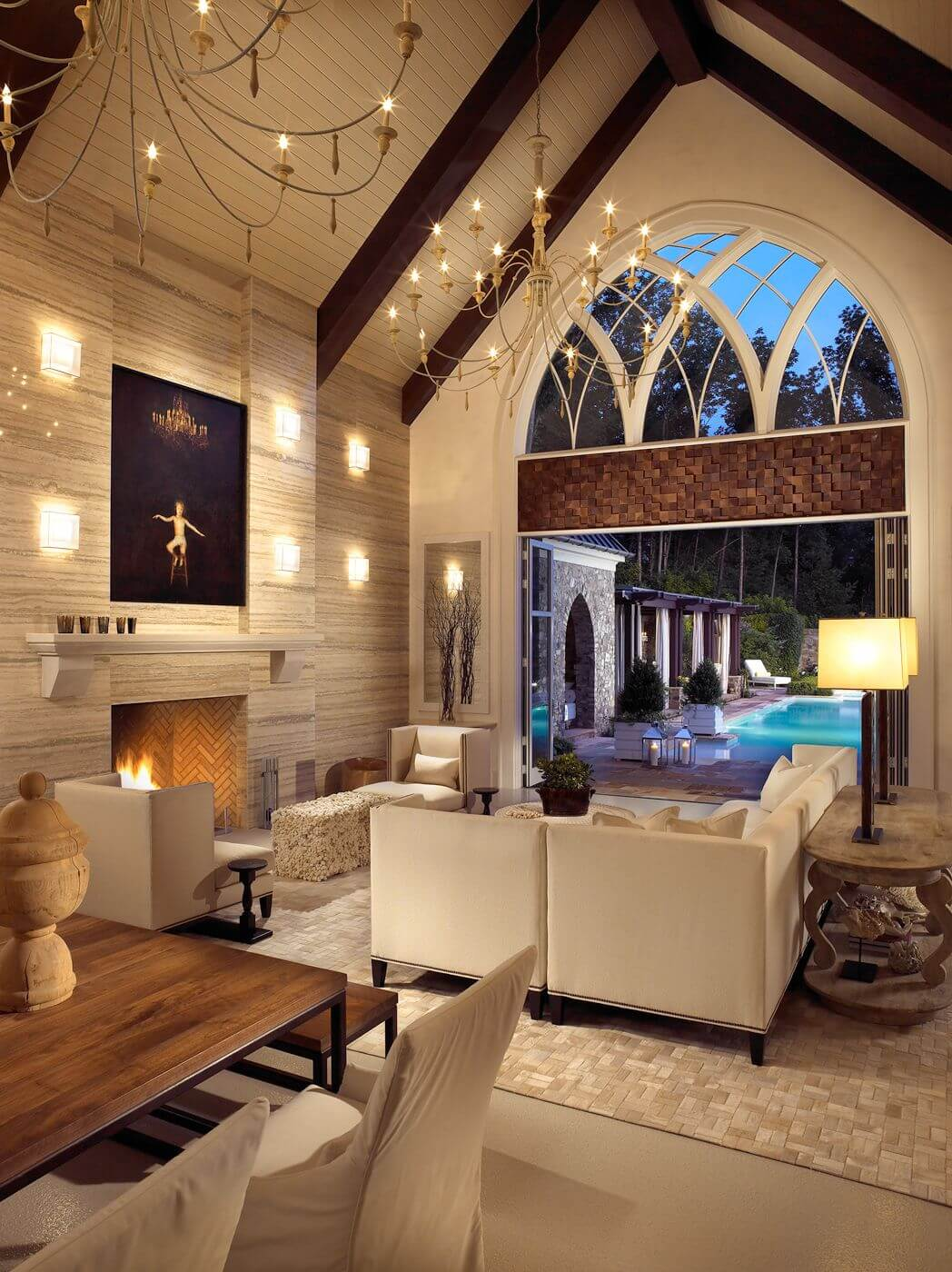 This luxurious room features an L-shaped living room sectional in beige, near large sliding patio opening. Rich stone textures and high vaulted ceiling with exposed beams complete the look.