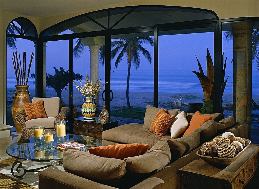Tropical Themed Living Room Is Filled With Grey Pillow Backed Sectional,  Glass Topped Coffee Table