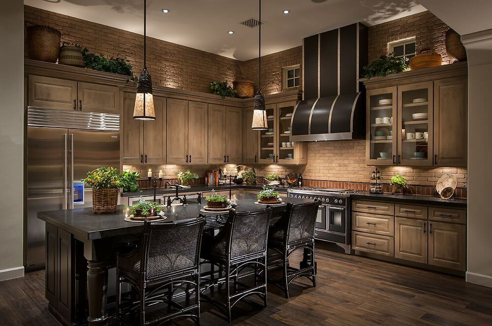 Brown tile walls match wood cabinetry and darker hardwood flooring in this kitchen centered around black island with full dining space.