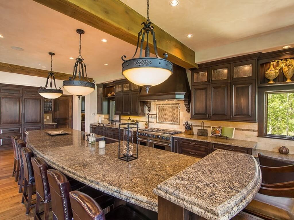 Open kitchen features this lengthy island with dining seating and brown marble countertop, with dark wood cabinetry and tile backsplash beneath trio of chandeliers and exposed ceiling beams.