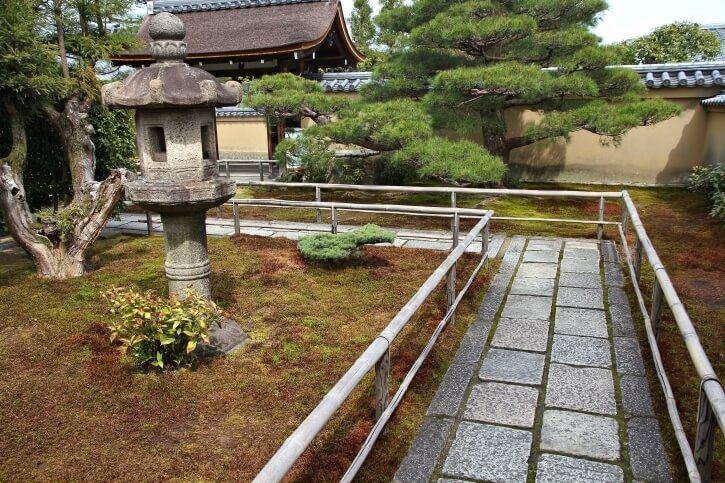 This Japanese Garden Features Well Worn Stone Walkway Between Bamboo Rails.