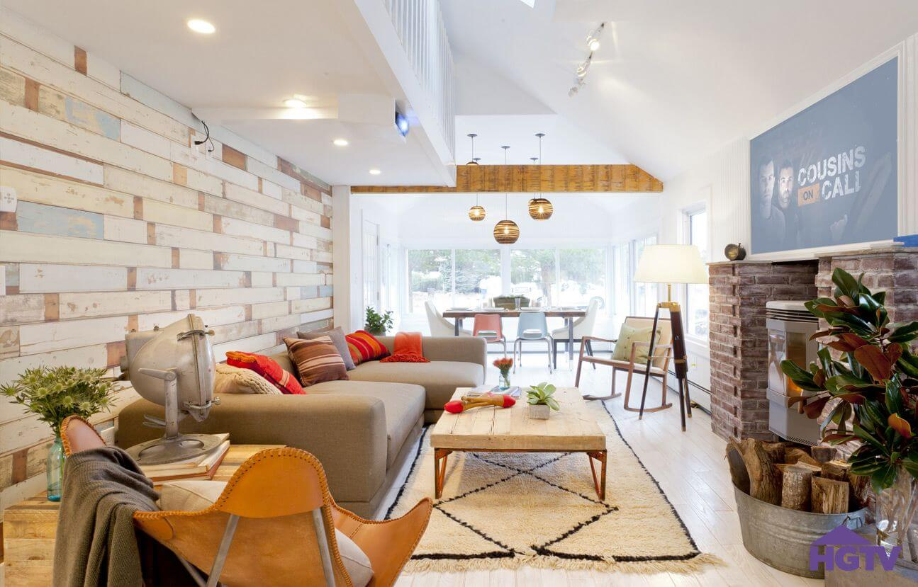 This Bright Living Room Featuring Textured Wood Panel Wall Under White  Balcony, With Brick Fireplace