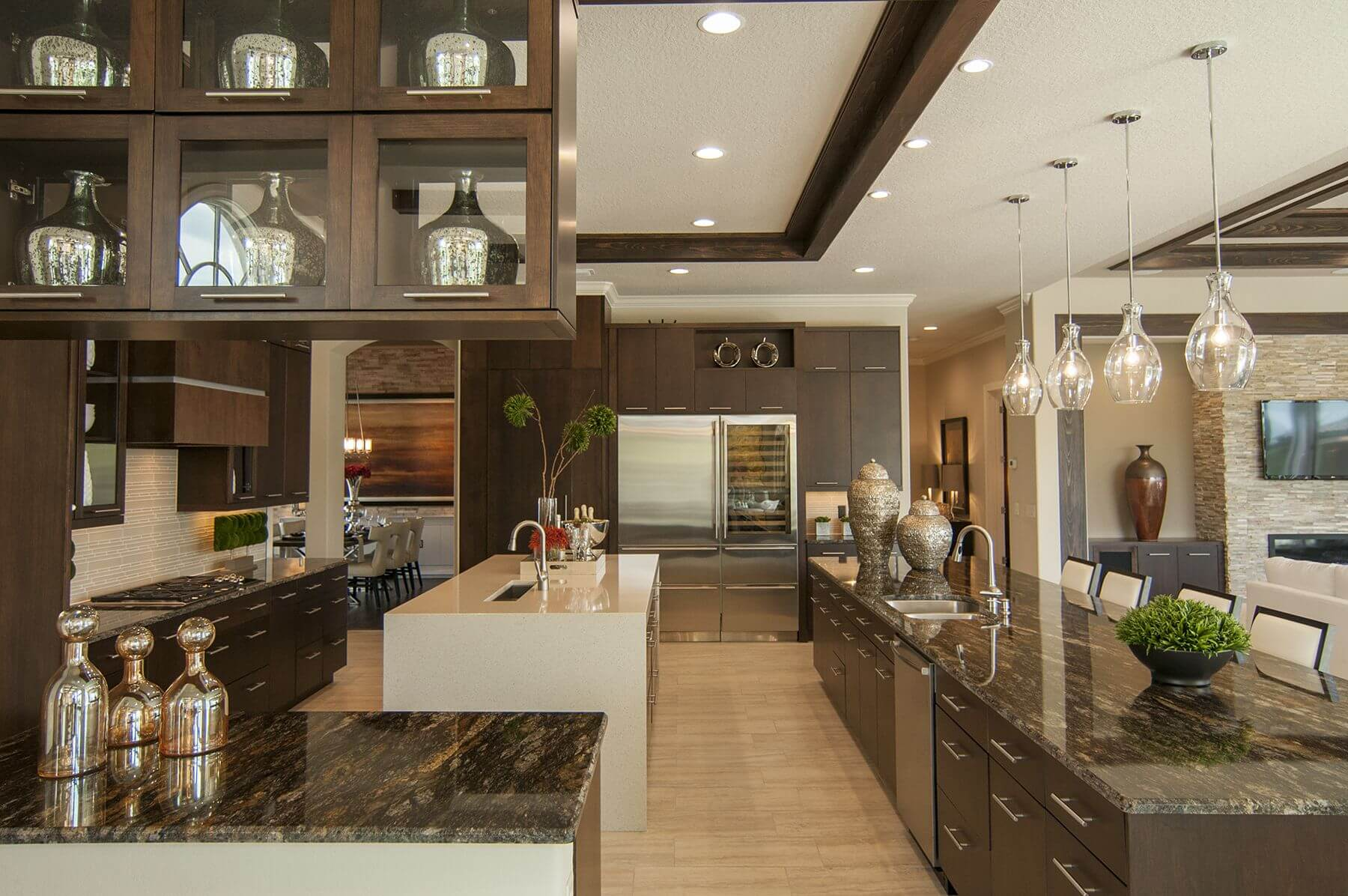 Ultra-modern look kitchen flush with dark tones: marble countertops, minimalist wood cabinetry paired with light hardwood flooring and white tone island in open design.