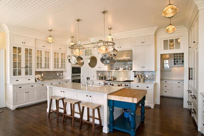 white kitchen featuring large white island with attached blue segment featuring large natural wood cutting - Large Kitchen Layouts