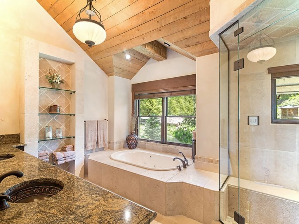 Bathroom awash in marble, with light beige marble flooring, bath, and shower construction and dark marble vanity countertop. Glass door shower and bath sit beneath windows, while more exposed beams feature in the ceiling.