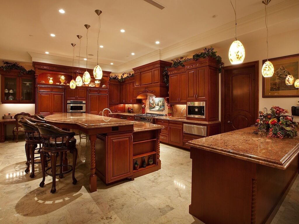 Luxurious Open Kitchen With Stained Wood Cabinetry And Large Two Tier Island At