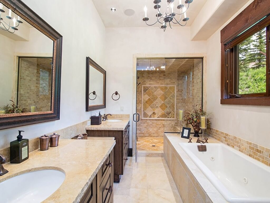 This bathroom features twin marble topped vanities across from large jacuzzi tub beneath window, with oversize walk-in glass door shower at center.