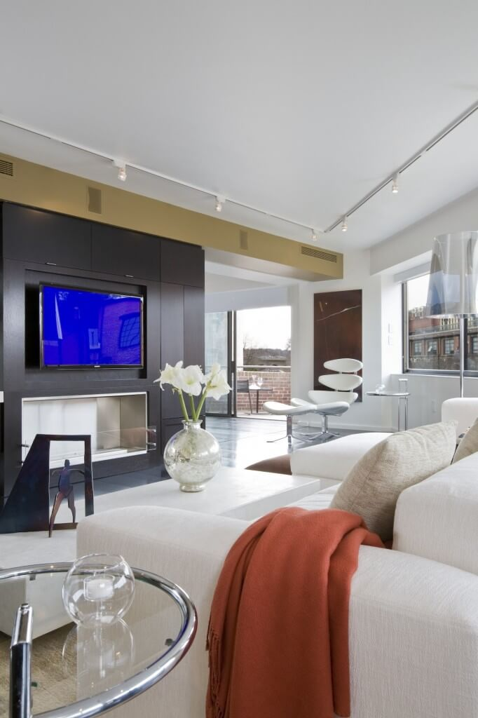 Opposite angle of living room reveals ultra-modern gas fireplace under mounted television, with open space leading to balcony in distance.