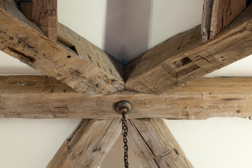 Ceiling center where all exposed natural wood beams meet, supporting large central chandelier.
