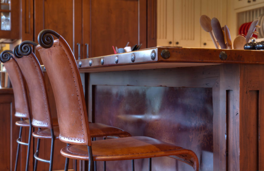 Up-close view of leather seating at island reveals details like rivets on the countertop and carved wood detail.