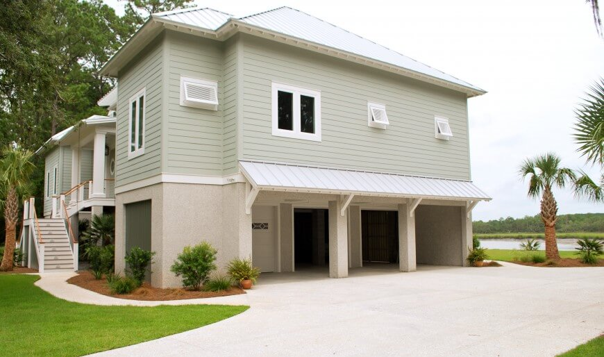Side of home features three port garage with covered entryway.