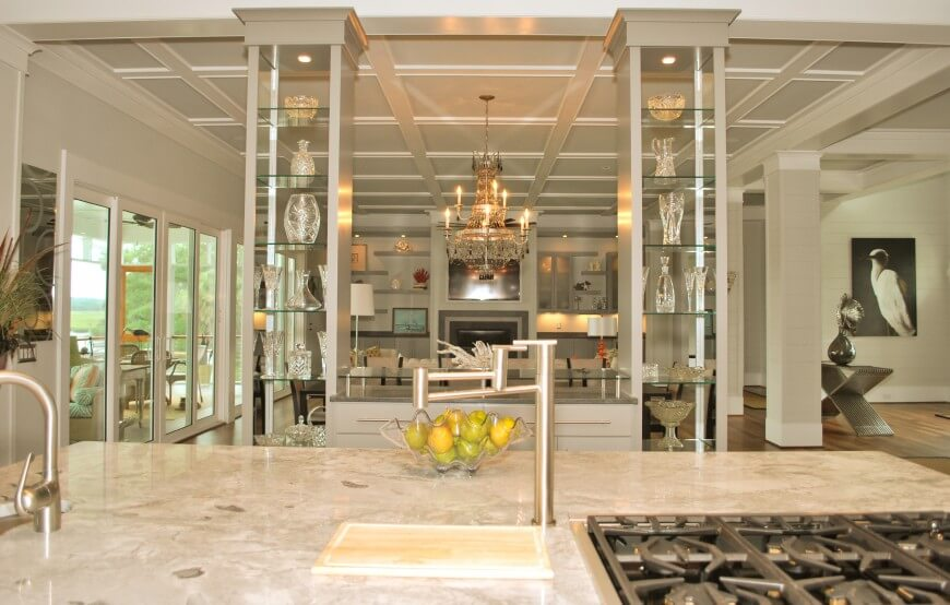 View over kitchen island with built-in range. Curio style pillar shelving holds glass pieces, with living room seen in background.
