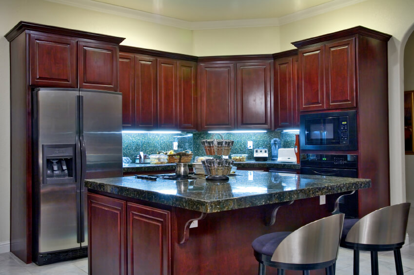 black and stainless kitchen heres a corner kitchen decked out in dark cherry wood with dark forest green marble countertops