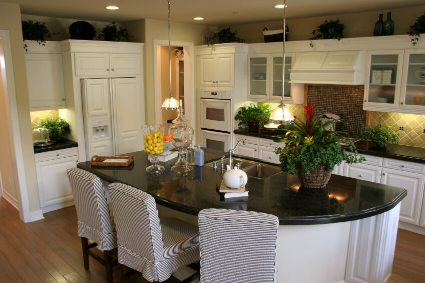 White kitchen features matching island with contrasting black countertop, full dining seating and built-in sink.