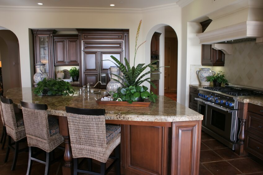 Natural wood paneling under light marble countertop define this wedge-shaped island with full dining space.