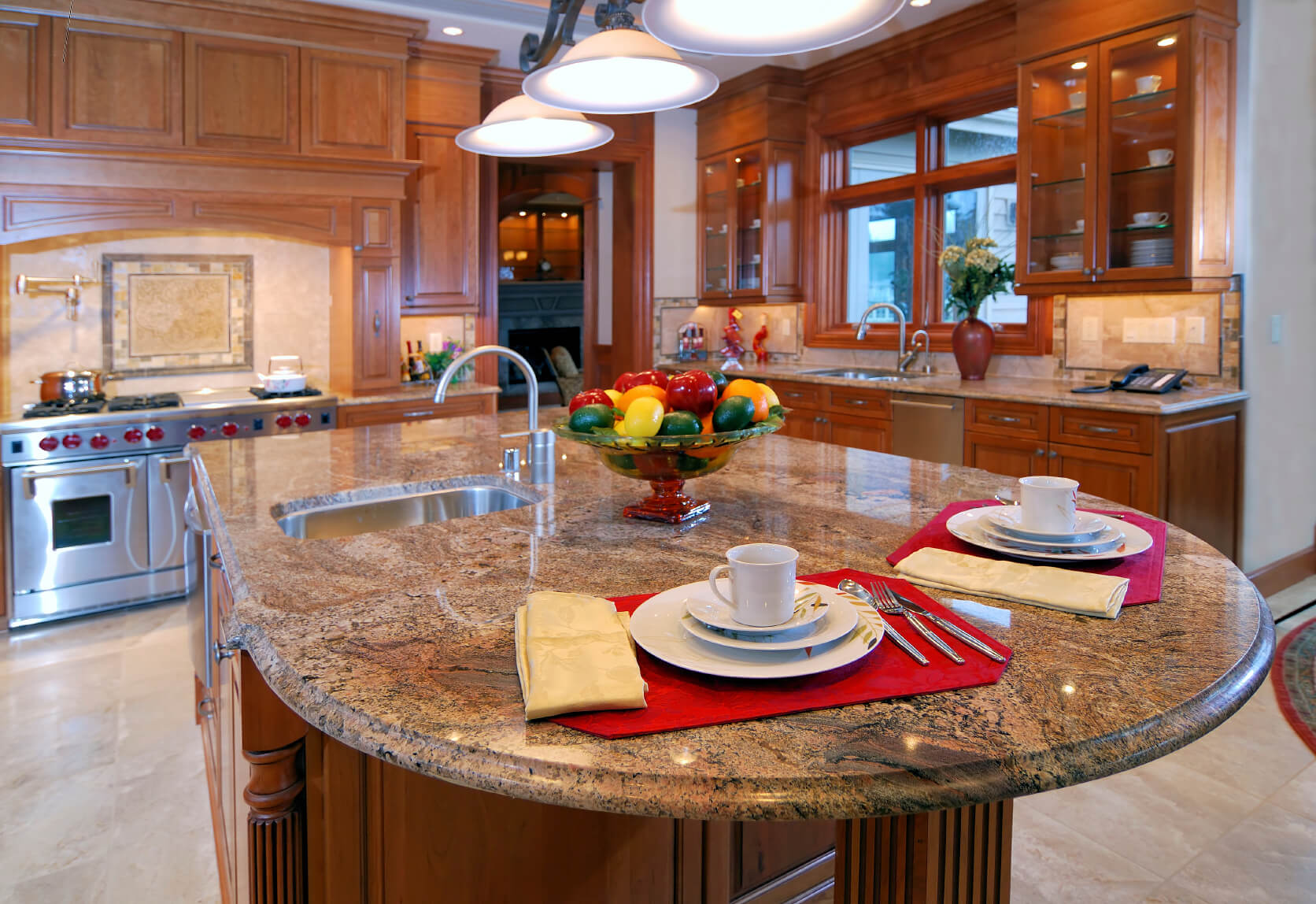 Kitchen island custom designs - Rich Patterned Marble Countertop Extends To Round Dining Space On This Natural Wood Island