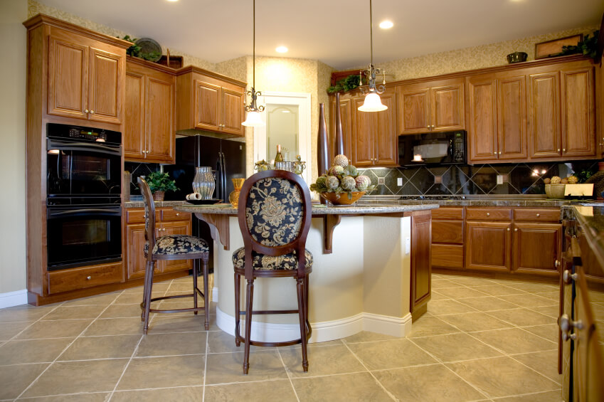Compact, detail-rich island sits at the center of this natural wood kitchen,