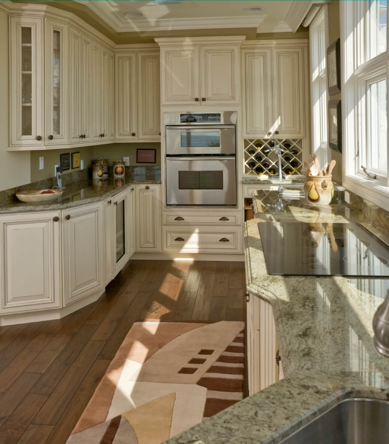 dark green island with beige marble countertop in this sunlit kitchen