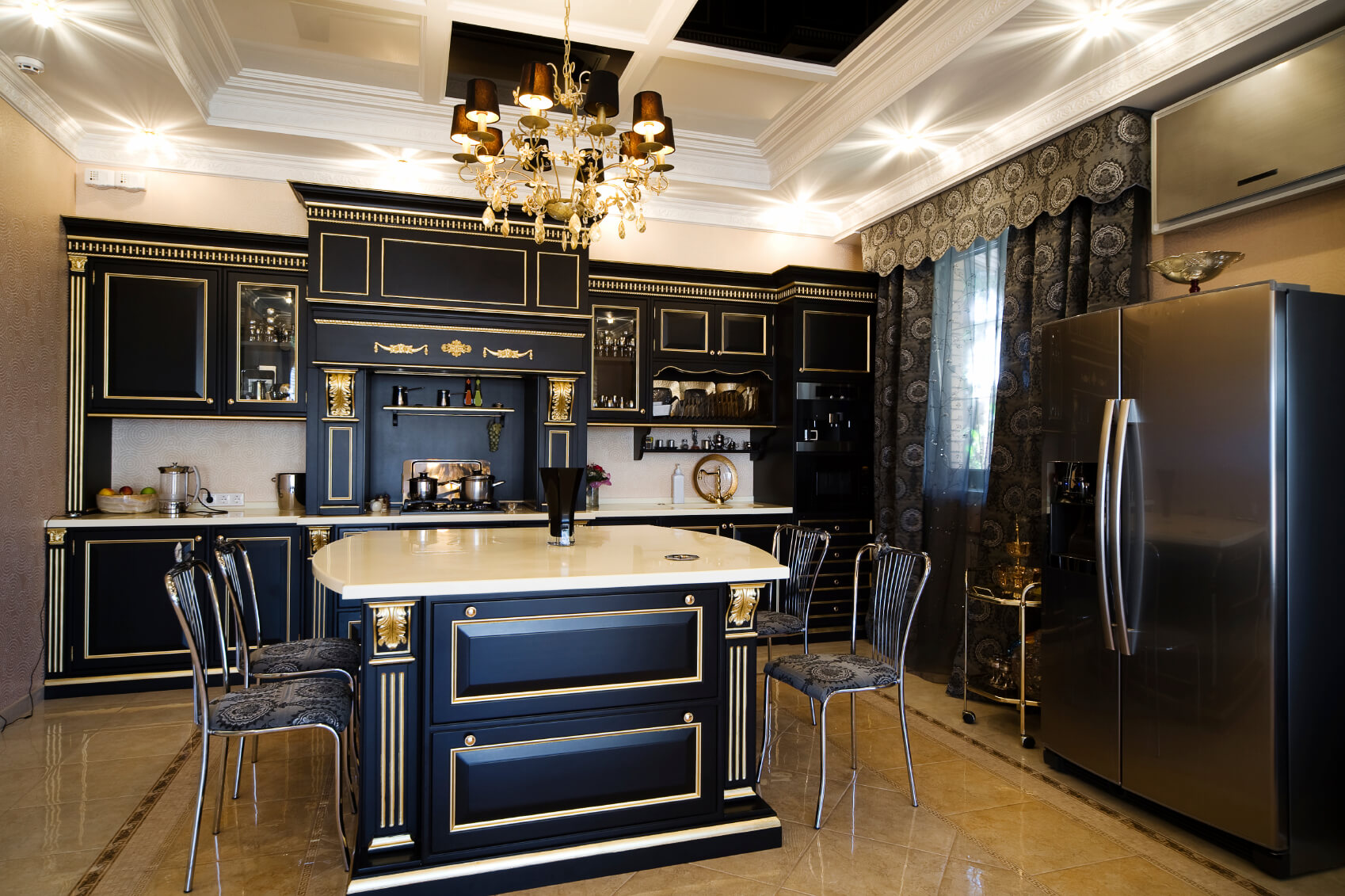 Ultra luxurious kitchen features gilded black wood cabinetry over beige marble flooring. White marble countertops and backsplash fills out the space.