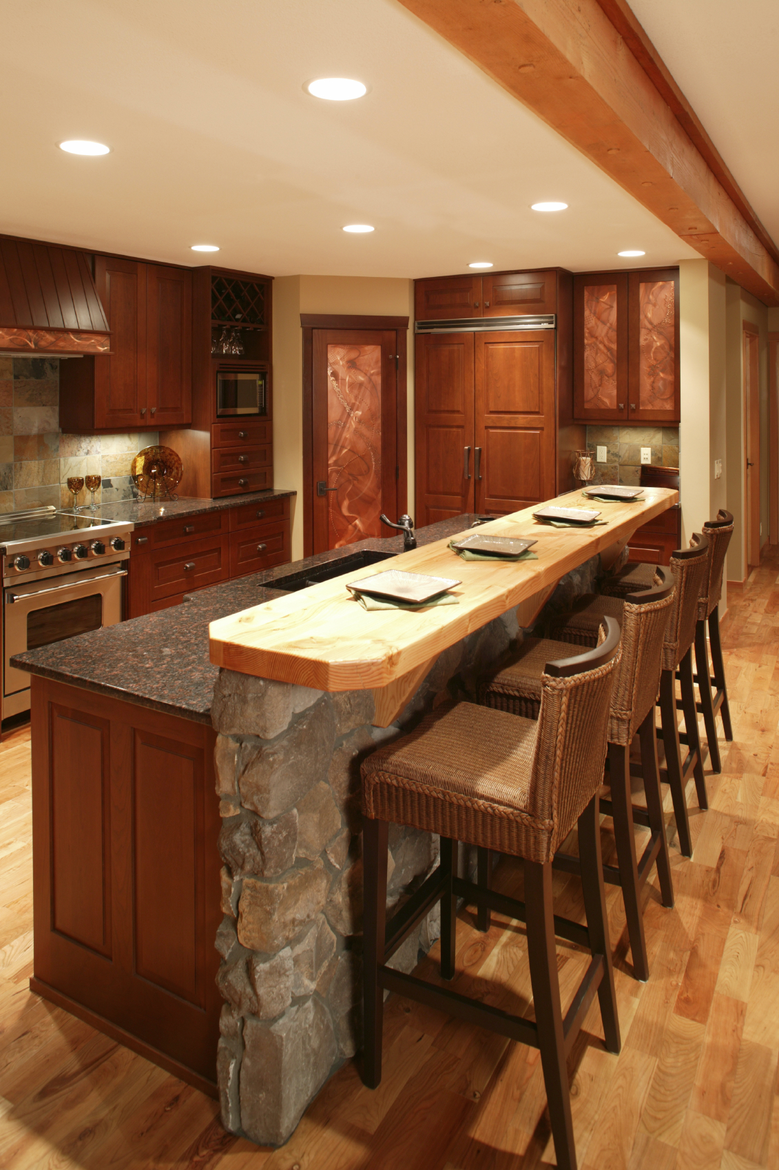 nice Kitchen Island Tops Ideas #9: Island comprised of stone wall and rich wood paneling matching the  cabinetry throughout this kitchen,