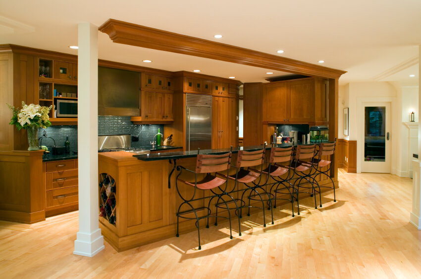 Kitchen space stands as part of larger open area, featuring warm wood paneling on every vertical surface and black marble countertop attachment for dining area.