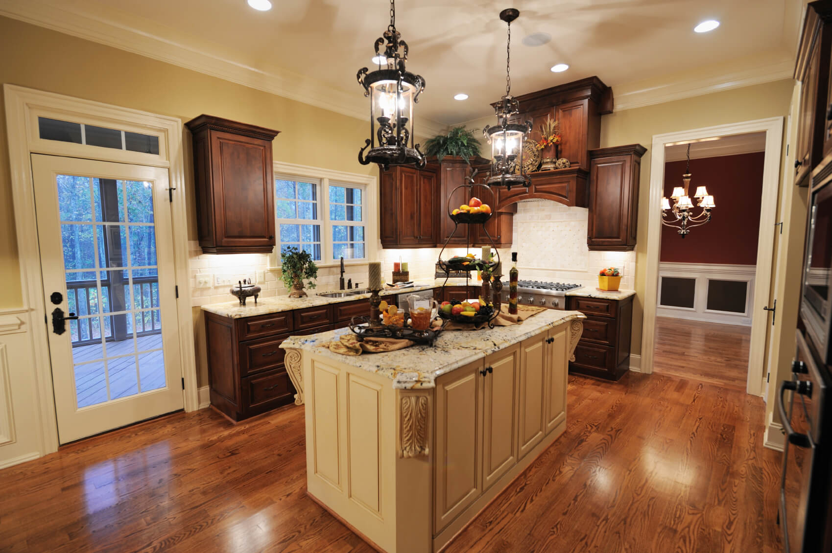 Lush dark wood cabinetry contrasts with beige island and wall color in