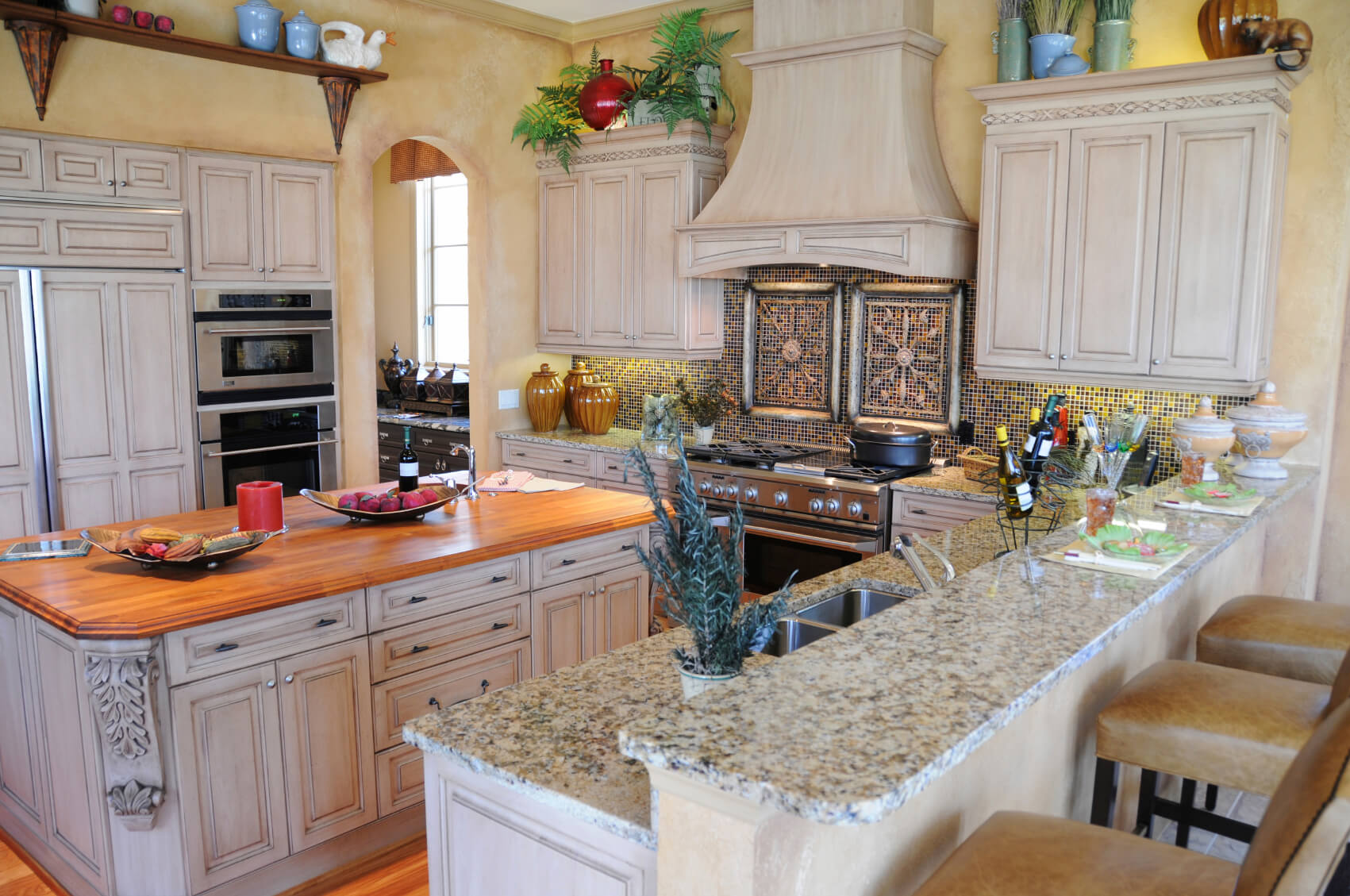Light painted wood island features bright natural wood countertop, matching hardwood flooring in this detailed kitchen.