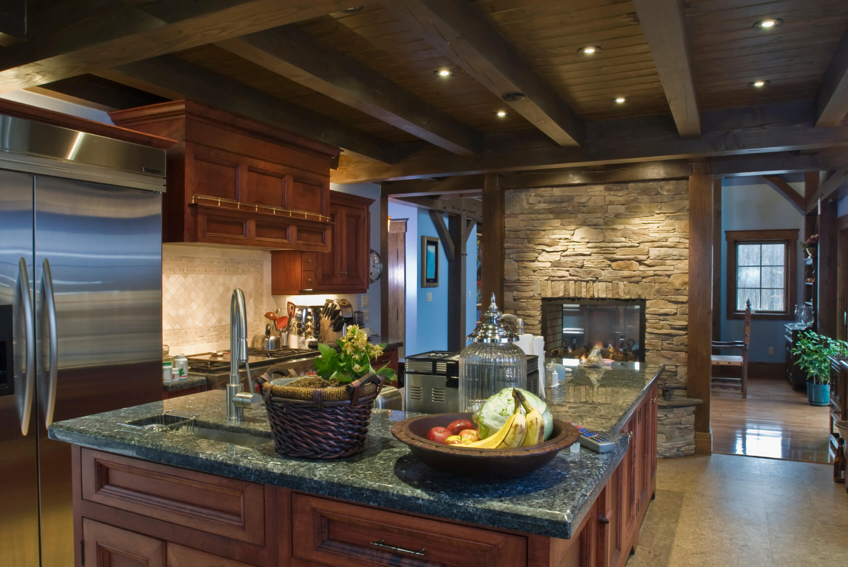 rustic look kitchen features brick pass through fireplace under dark wood exposed beams with