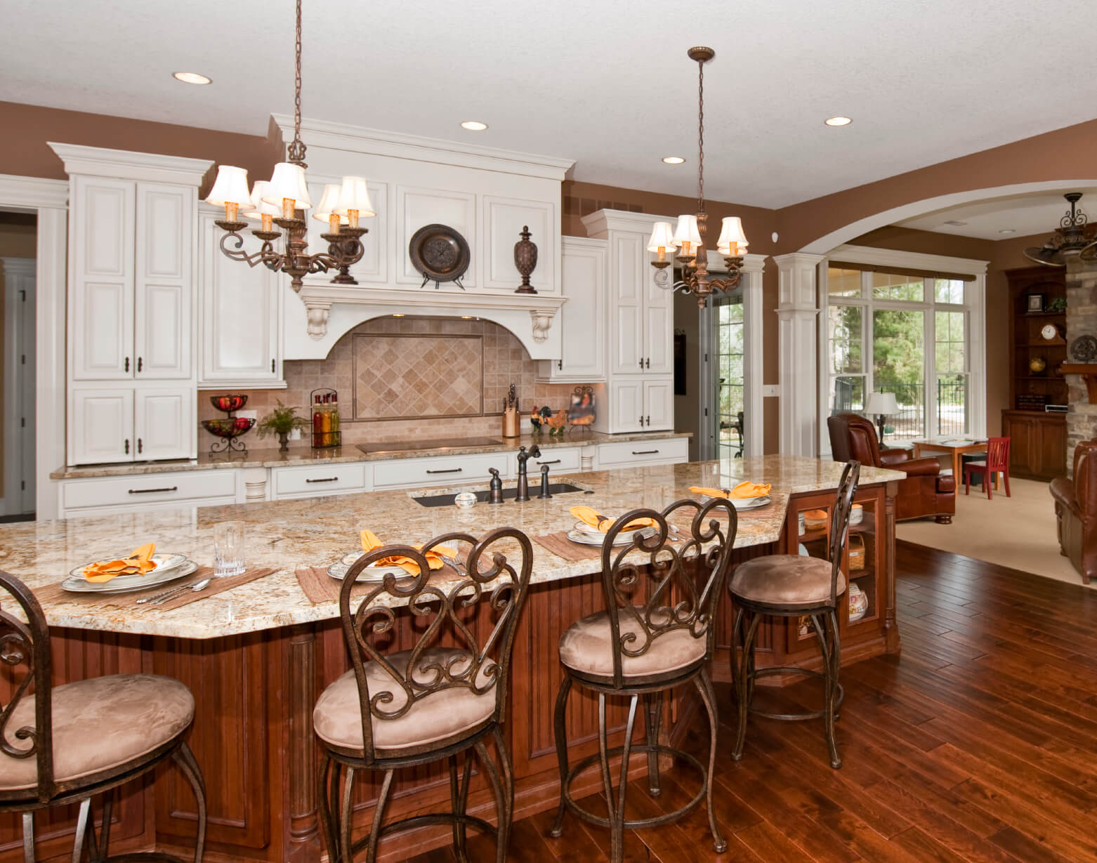 Large, open kitchen features immense island done in natural wood tones,  with built-