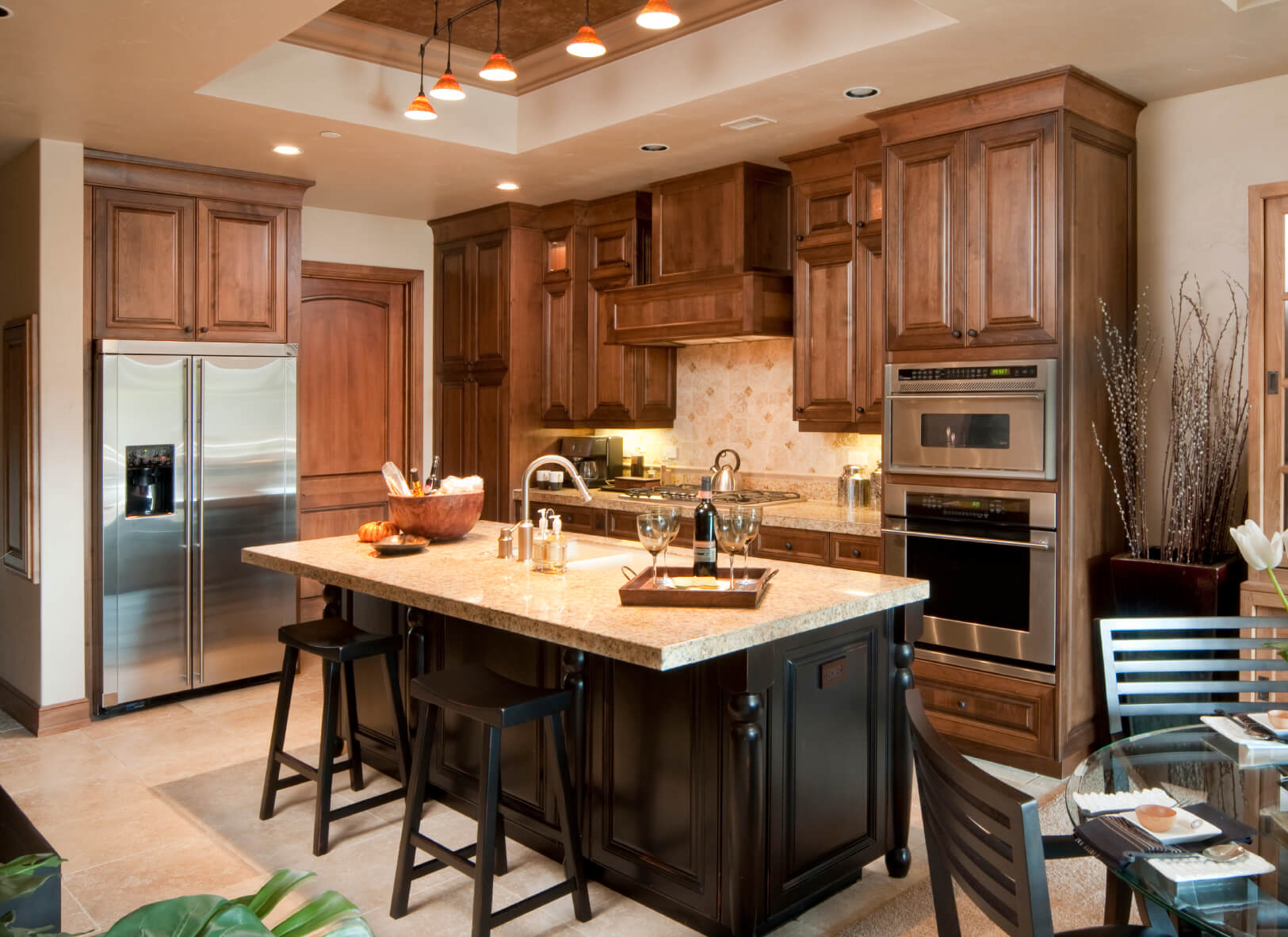 black wood and marble topped island commands center of this kitchen