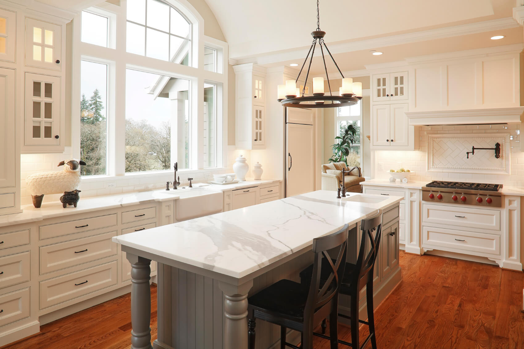 large ceiling height window affords natural light in this white kitchen centered around large marble topped - Large Kitchen Layouts