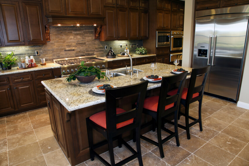 Large marble topped island with dining space centers this kitchen over  beige tile flooring, with