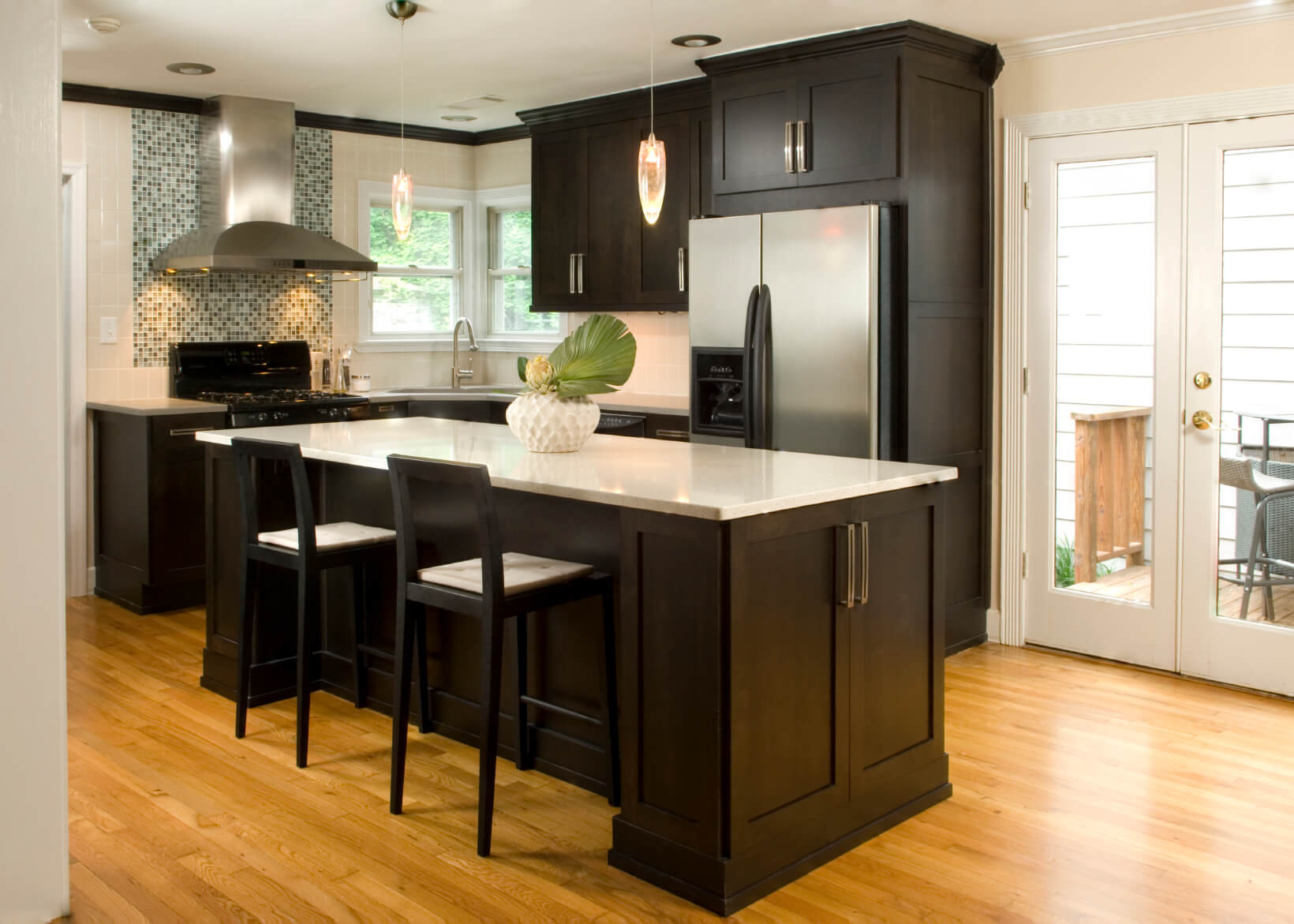 High Contrast White Wall Kitchen With Dark Wood Paneling And Cupboards Paired Countertops