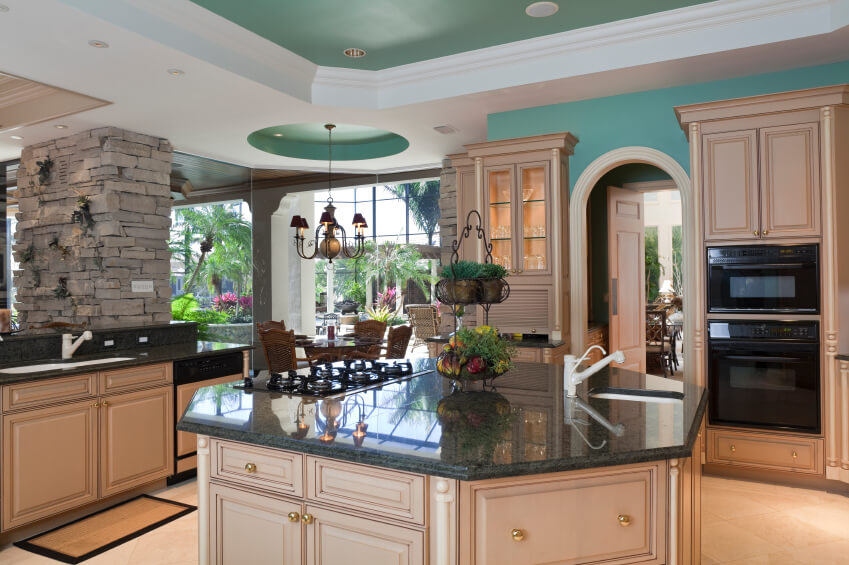 Lush green tones liven this kitchen, awash in beige wood paneling on cupboards and octagonal island. Island features built-in sink and range on forest green marble countertop.